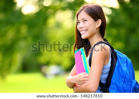 University / college student girl looking happy smiling with book or notebook in campus park. Beautiful young mixed race Asian Chinese / Caucasian young woman female model. - stock photo