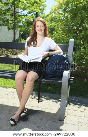 University / college student girl looking happy smiling with book or notebook in campus park. Beautiful young Caucasian young woman female model. - stock photo