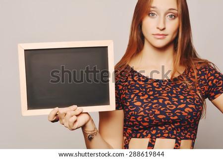 University college student holding a blackboard. Beautiful Caucasian young female model. - stock photo