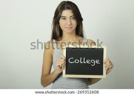 University college student holding a chalkboard / blackboard saying college. Beautiful Caucasian young female model. - stock photo