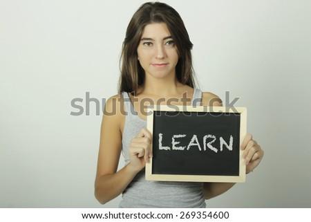 University college student holding a chalkboard / blackboard saying learn. Beautiful Caucasian young female model. - stock photo