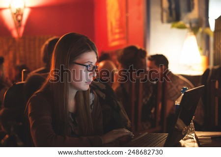 University female student working on laptop in a pub. Girl using computer in a public place to access social networks and the internet. Education concept. Image with vintage filter applied - stock photo