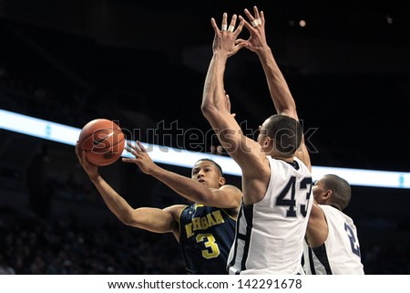 UNIVERSITY PARK, PA - FEBRUARY 27: Michigan's #3 Trey Burke shoots around 2 Penn State defenders at the Byrce Jordan Center February 27, 2013 in University Park, PA - stock photo
