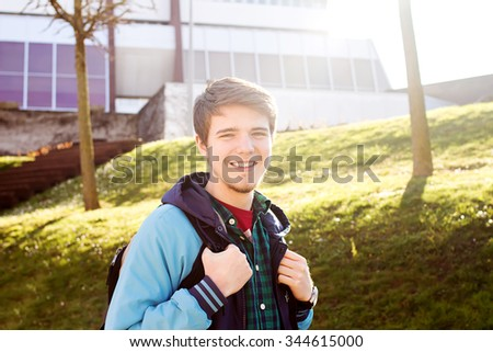 University.Smiling young student man holding a bag in sunrise on a university background .Young smiling student  outdoors Life style.City.Student.Campus - stock photo