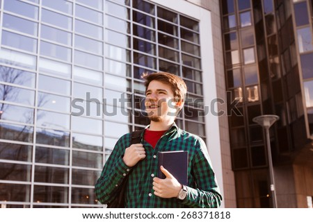 University.Smiling young student man holding a book and a bag on a university background .Young smiling student  outdoors Life style.City.Student. - stock photo