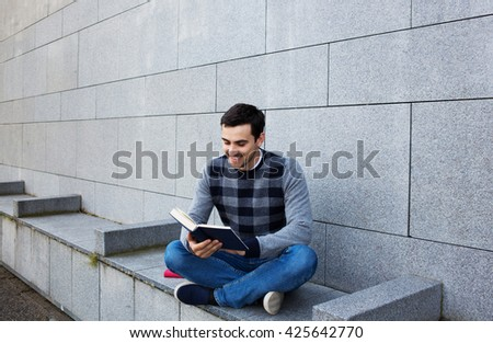 University.Smiling young student man holding nd reading book  on a university background .Young smiling student  outdoors Life style.City.Student. - stock photo