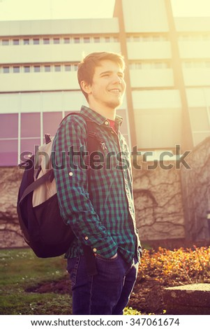 University.Smiling young student man with a bag on a university background .Young smiling student  outdoors Life style.City.Student. - stock photo
