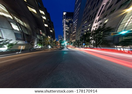 University Street in Montreal with silhouette cars with red rear light and traffic light, with offices buildings background, at dusk (4.5 mm Circular Fish eye Effect) - stock photo