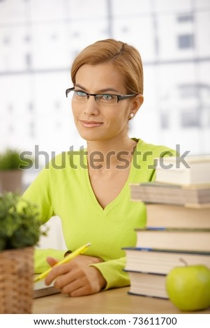 University student girl wearing glasses sitting at desk with pile of books holding pen, smiling.?