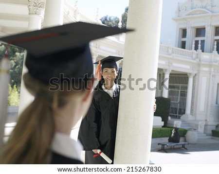 University student in graduation gown and mortar board holding diploma, smiling, focus on background - stock photo