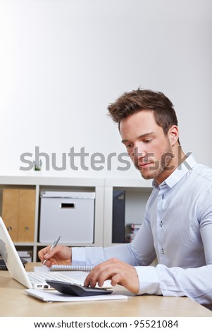 University student learning with laptop computer and calculator - stock photo