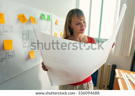 University student of Interior Design doing homeworks, reviewing housing project and completing project. The girl contemplates her blueprint and smiles. - stock photo