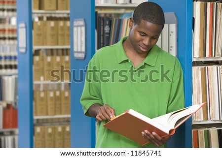 University student reading book in library - stock photo