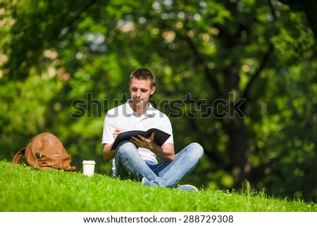 University student studying for exams outdoors in the park. With him his books, notebook, backpack and coffee. - stock photo