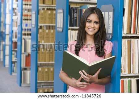 University student studying in library holding book - stock photo