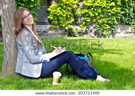 University student studying outside on campus - stock photo