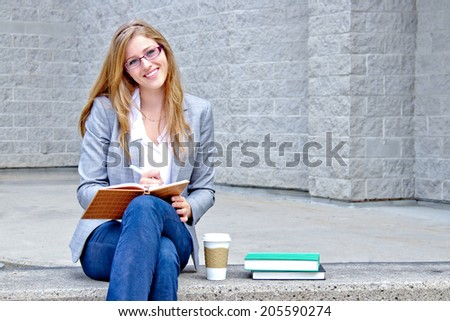 University student writing in a journal - stock photo