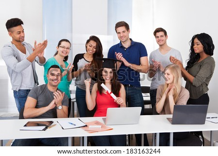 University students clapping for classmate holding degree in classroom - stock photo