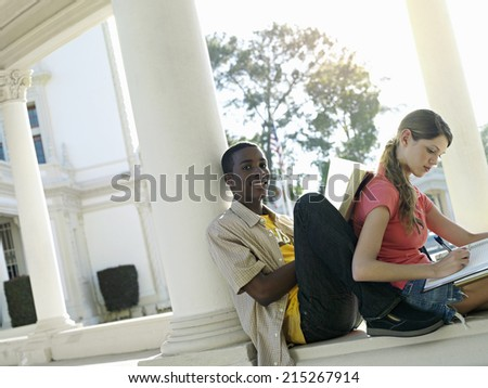 University students studying near colonnade, man leaning book against woman's back, smiling (tilt) - stock photo