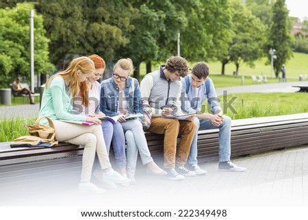 University students studying while sitting on low wall in park - stock photo