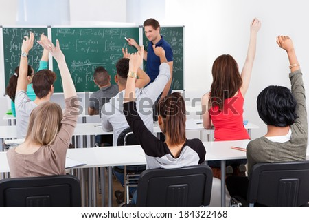 University students with arms raised answering teacher in mathematics class