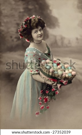 UNKNOWN - CIRCA 1915: An unidentified woman holds a basket of colored Easter egg in this Victorian Era hand-tinted portrait circa 1915 taken in an unknown location.
