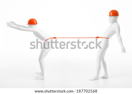 unknown men dressed in white suit, wearing protective helemts, held together by an orange rope around their waist - stock photo
