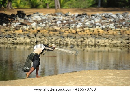 Unknown traditional Fishermen who throw the fishing nets at a beach in daylight. - stock photo