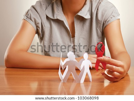 Unknown woman taking care about paper people and aids, isolated on grey - stock photo