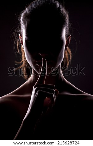 unknown woman with the face in the shadow holding finger on lips - stock photo