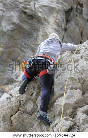 Unknown young woman climbing on the rock