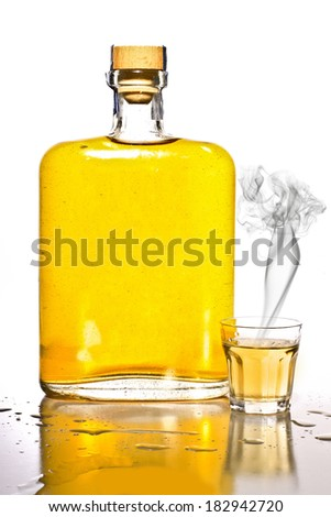 Unlabeled bottle of tequila next to a shot glass with smoke. - stock photo