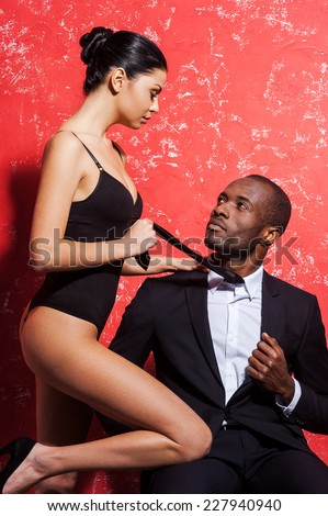 Unleashed desire. Handsome young African man in formal wear sitting at the chair while beautiful woman in lingerie bonding to him and stretching his necktie - stock photo