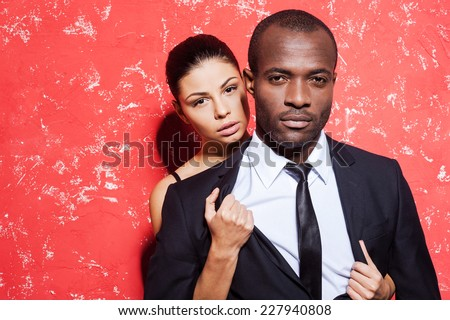 Unleashed desire. Handsome young man in formalwear standing against red background while woman taking off his jacket - stock photo