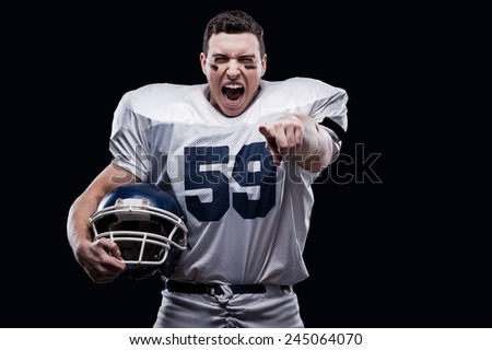 Unleashed emotions.  American football player screaming and pointing at camera while standing against black background  - stock photo