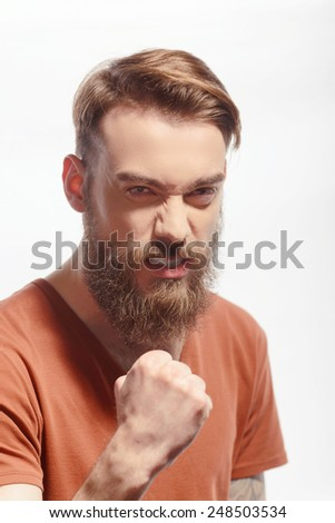 Unleashing his emotions.  Portrait of handsome tattooed bearded man wearing orange tshirt and showing his fist with angry face expression while standing against white background - stock photo