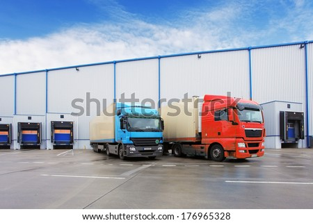 Unloading cargo truck at warehouse building - stock photo