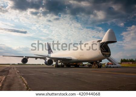 Unloading wide-body cargo aircraft - stock photo