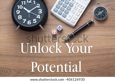Unlock Your Potential written on wooden table with clock,dice,calculator pen and compass - stock photo
