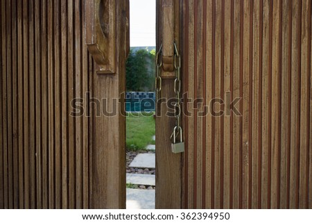 Unlocked metal chain on old wooden doors with green garden and private pool behind. - stock photo