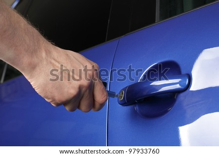 Unlocking a car door with a key - stock photo