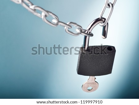 Unlocking a padlock securing two metal chains with blue background - stock photo