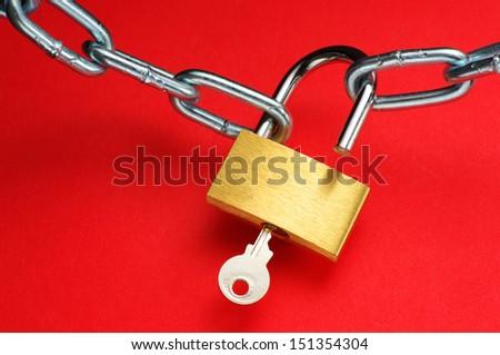 Unlocking padlock. Unlocking padlock and chain on red background.  - stock photo