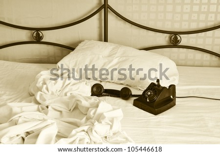 Unmade bed with old bakelite phone with receiver off. - stock photo