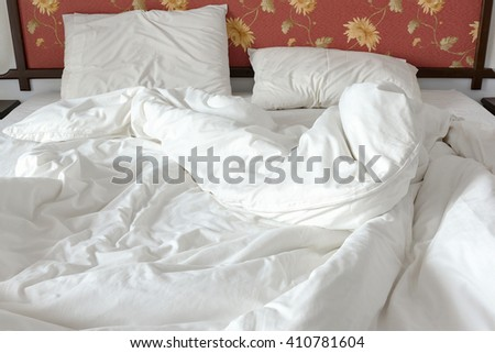 Unmade / untidy bed with a white crumpled blanket and two messy pillows in a bed room. Bedclothes are not neatly arranged for new customers / guests to sleep in. View from the foot of the bed. - stock photo