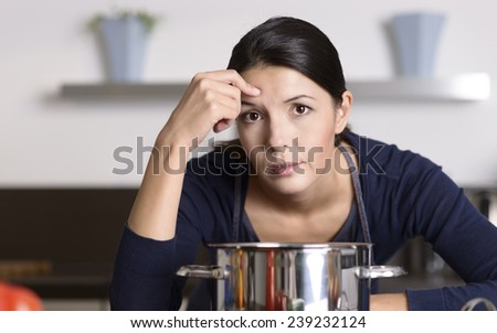 Unmotivated attractive young woman preparing the dinner leaning on the hob eyeing the camera with a listless glum expression as she stands in her kitchen in an apron - stock photo