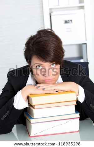 Unmotivated businesswoman seated at her desk with her hands and chin resting on a high pile of books - stock photo