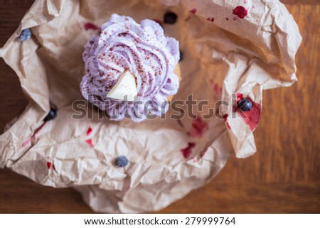 Unpacked blueberry muffin with white chocolate on top - stock photo