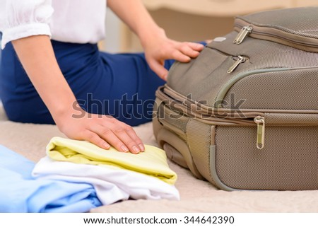 Unpacking time. Young nice-looking female tourist opens suitcase and starts unpacking.  - stock photo