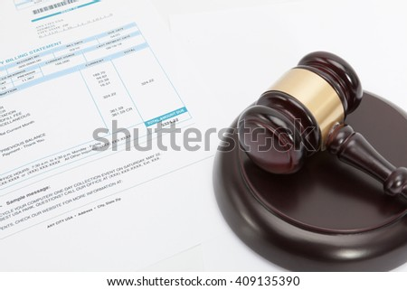Unpaid bill with wooden gavel over it - stock photo